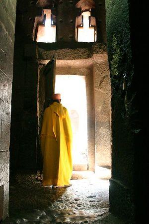 priest in yellow robe, lalibela, ethiopia