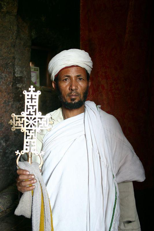 priest and church cross, lalibela, ethiopia
