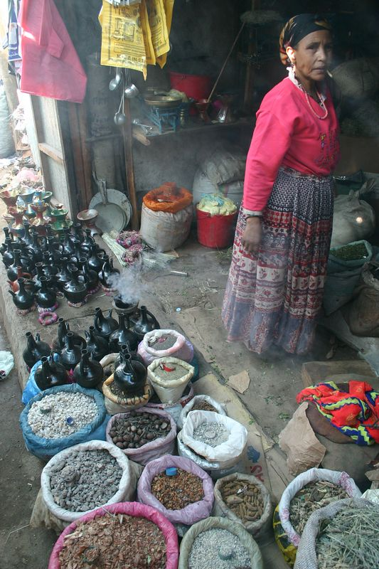 woman selling incense and coffee pots at the christian market, harar, ethiopia