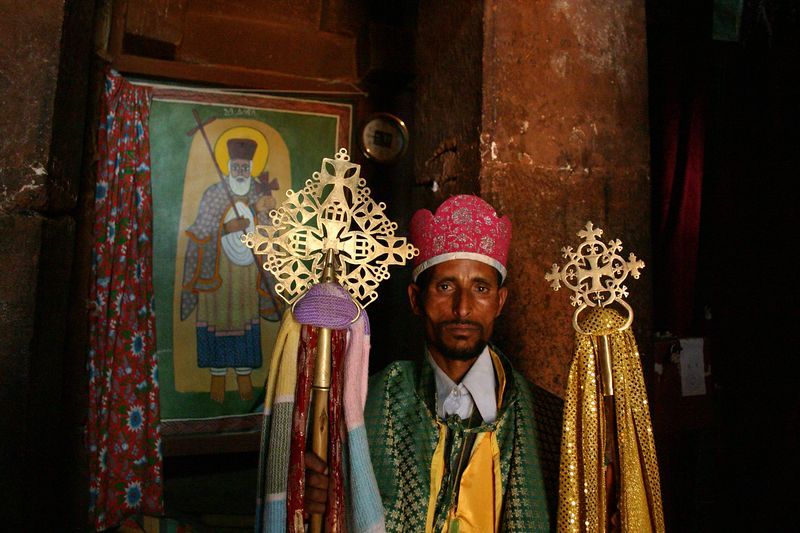 priest with church crosses, lalibela, ethiopia