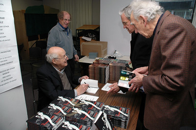 Eric Koch signing books at the launch on December 4, 2010. At right, Fred Langan and Horace Krever.