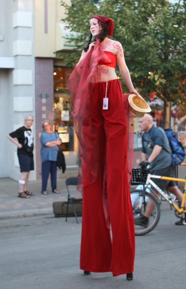 A couple observes a woman standing on stilts.