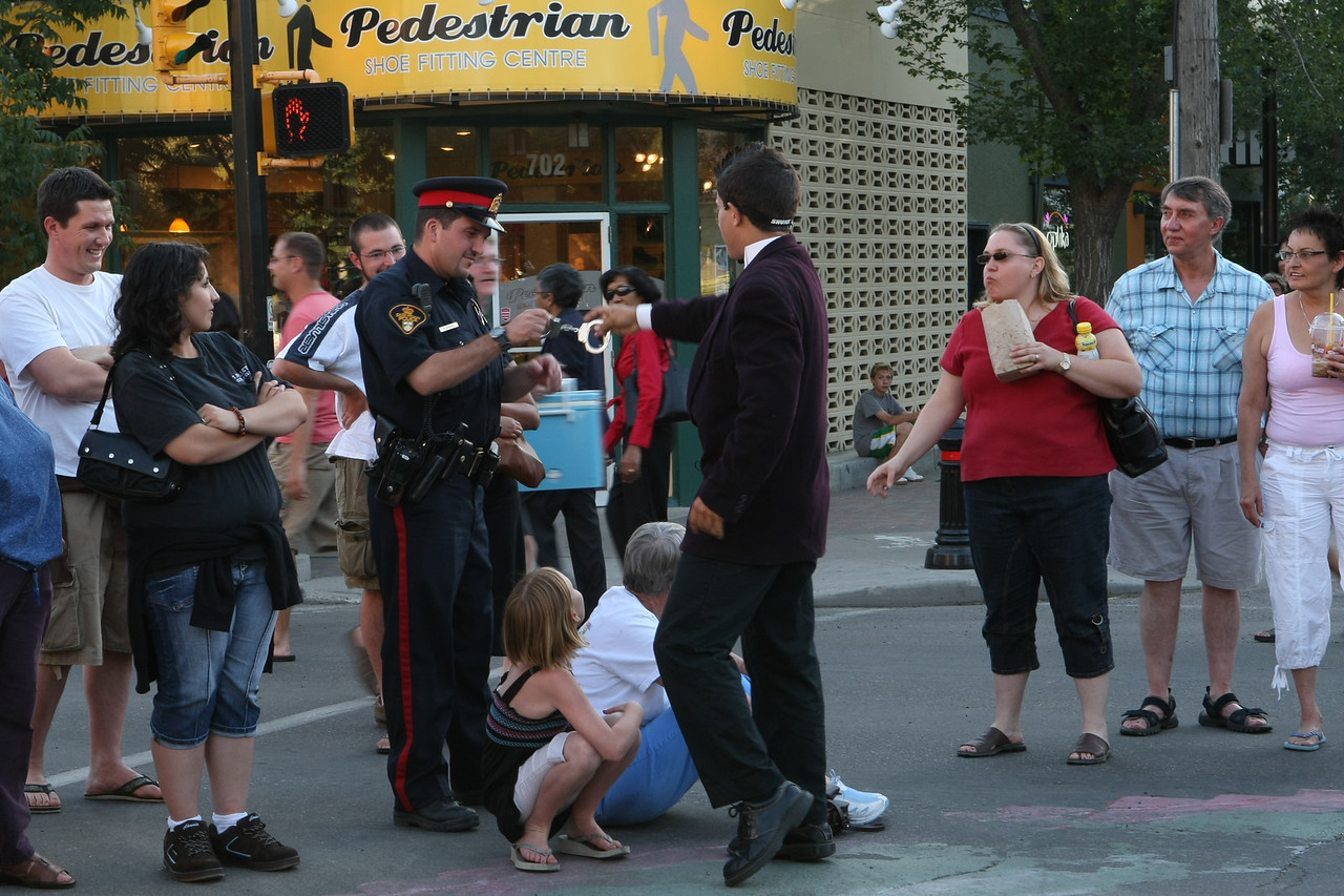 A Saskatoon City Police officer inspects handcuffs as authentic.