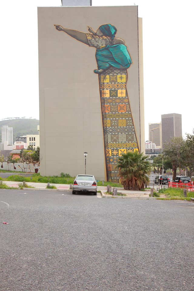 Street art against the side of a tall building  in Cape Town: woman with a child on her back