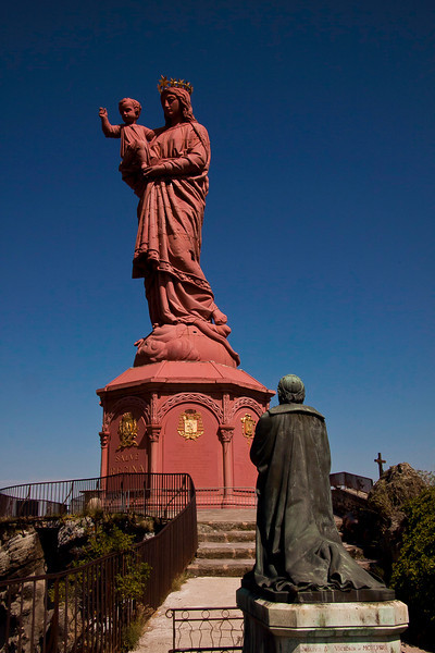 Le Puy en Velay - Haute Loire - France<br /> La statue Notre-Dame de France mesure 22,70 m (16 m + 6,70 m de piédestal) et pèse 110 tonnes. Elle représente la Vierge, Reine du Ciel et de la Terre, écrasant un serpent (victoire du Bien sur le Mal). Elle porte son Fils à qui elle présente la ville pour qu'il la bénisse. Plus généralement, cette statue montre une mère bienveillante protégeant son fils des dangers et le portant pour qu'il découvre le monde.