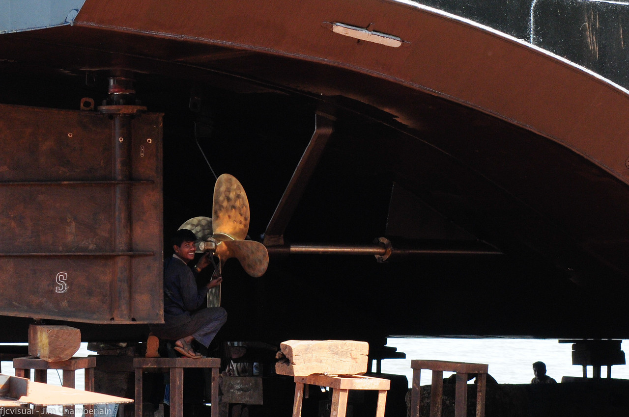 A young man works on a ship propeller at a ship yard in Panjim Goa, India.