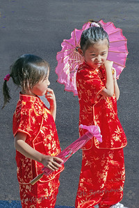 Little Ladies Two ~ These children were playing at the side of the street, waiting for the Chinese Lunar Parade to come by.  I liked their matching outfits and parasols.