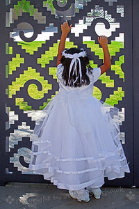 The Grass is Always Greener ~ On Saturdays the church at Olvera Street holds baptisms and first communions.  Many children of various ages come dressed in their fancy white dresses or little white suits, and wait in line with their parents for their own ceremony.  This girl was near by the church, looking through the ornate metal fence; I liked the juxtaposition of soft against hard.