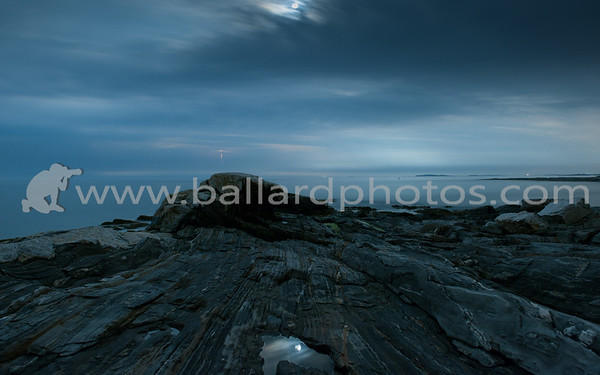 Peering over the rocks into the Gulf of Maine, a bolt of lightening from a distant storm. Pemaquid Point,  New Harbor, Maine