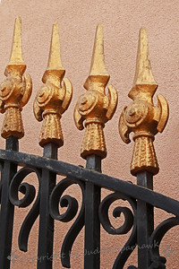 Spires of Gold ~ Gate details show against the stucco wall.