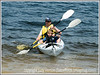 A father and son paddle their kayak in a Colorado mountain lake.