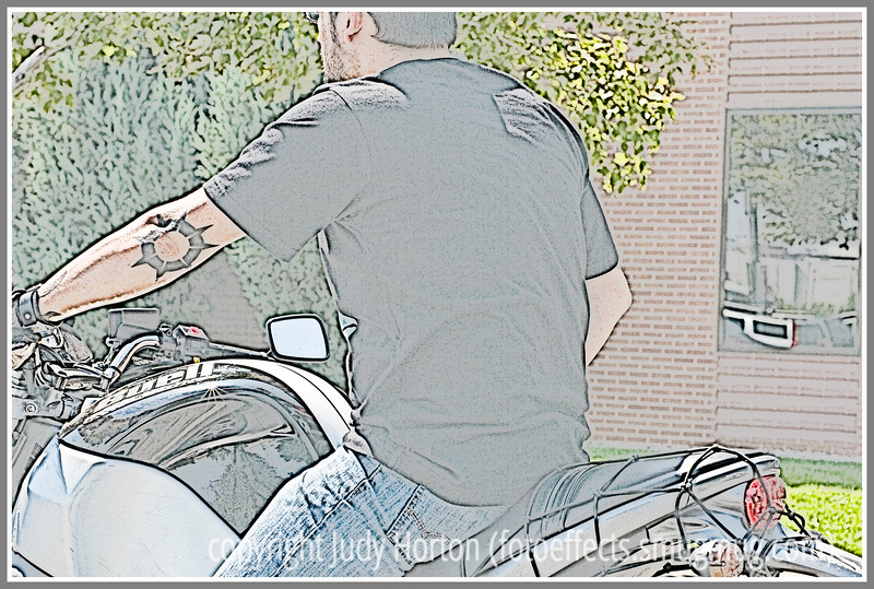 A man on a motorcycle; the image has been manipulated in Photoshop to make it look more like a silkscreen print.
