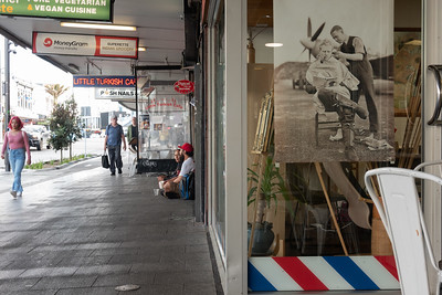 Karangahape Road street scene of barber shop window and people un footpath includining two sitting and begging