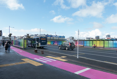 Pink cycle lane on footpath between bus stop and glass wall on the city's Karangahape Road