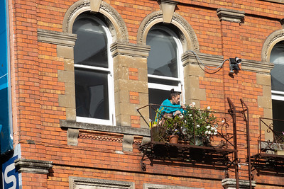 Woman in blue tends flower through window in traditional red brick building.