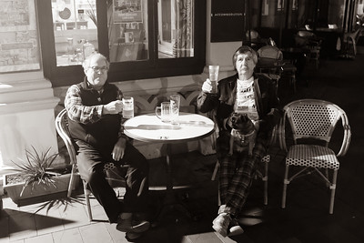 Two patrons seated outside historic Esplanade Hotel in Devonport with their dog and beer.