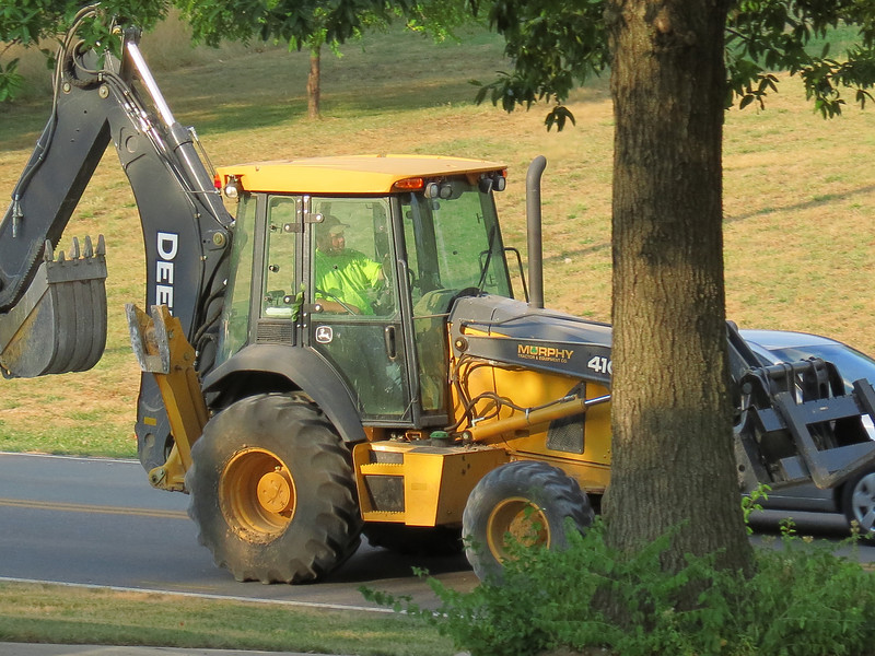John Deere backhoe loader driving past the house.<br /> One of the excavating machines that is replacing a water main on our street - but not our water main.<br /> The temperatures are very hot and drought has a firm grip on the area.