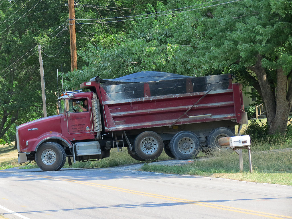 Red dump truck delivering crushed rock for the water main project.