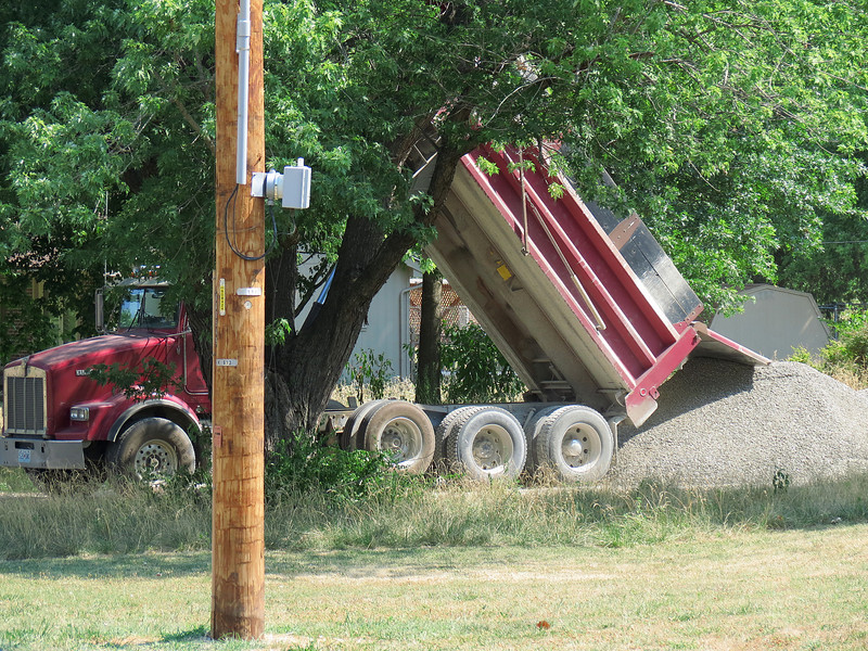 Red dump truck dumping the load of crushed rock.