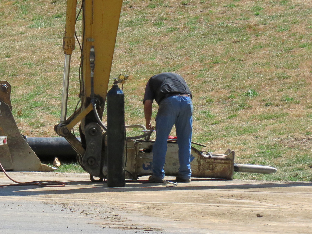 The hydraulic jack hammer has broken down and a repair technician is fixing it.<br /> The jack hammer attachment for the excavator is a useful tool when rock is encountered.<br /> It is fairly easy to detach the digging bucket and slip the jackhammer on when needed.