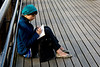 A girl scribbling in her diary on a pier, Southbank, London