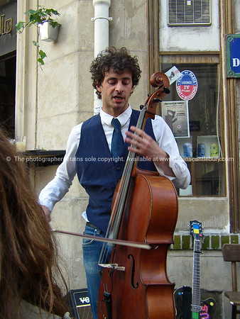 Cellist playing on street corner, Paris, International City.