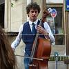 Cellist playing on street corner, Paris, International City.