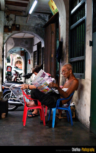 "Another old couples resting outside thier house and reading the ""late night"" newspaper."