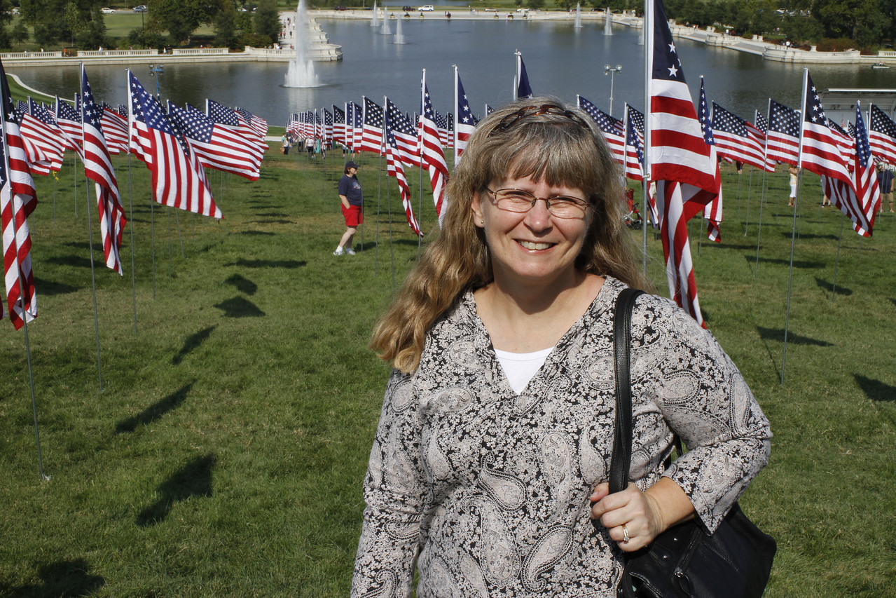 Rows and rows of American flags line the field of Art Hill in Forest Park.  Each flag pole has a name of a 9-11 victim.  Here's Cyndy participating in the remembrance of 9-11 on the 10th anniversary of this horrific tragedy with the Grand Basin behind her.  A group of 300 volunteers set up 2,9996 flags commemorating those that perished that beautiful, sunny, late summer day in 2001... one for each victim.