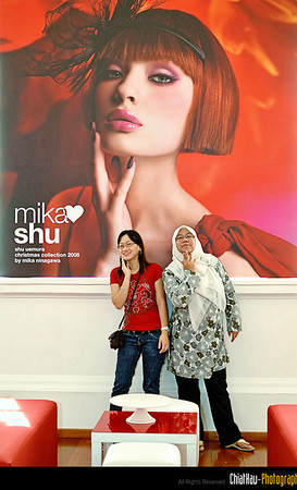 """Ee Lean and Siti posing in front of the bill board of """"Mika Shu""""."""
