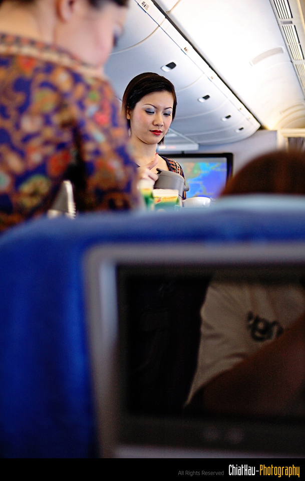 Stewardess is busy serving the food to the passanger inside the plane.