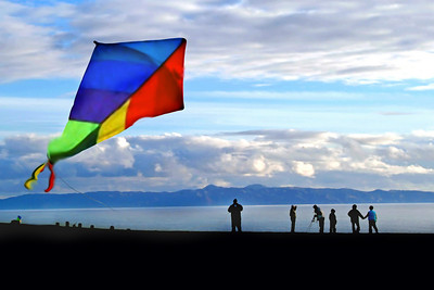 The soft blues of the sky, ocean and the distant Catalina Island paint a perfect background for the bright hues of a kite blowing against the wind while passersby take in the view at Angel's Gate Park.