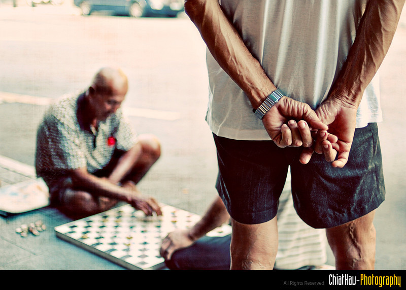When I turned around, I noticed that an uncle is watching some board game playing at the road side...