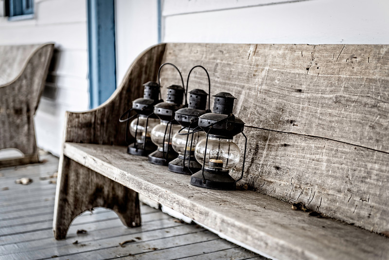 four lanterns on a bench, on a porch in Mooresville, Alabama
