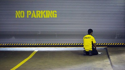 A Muslim parking valet seeks a quiet moment to pray near a dormant parking garage entrance one evening. (Houston, TX.)