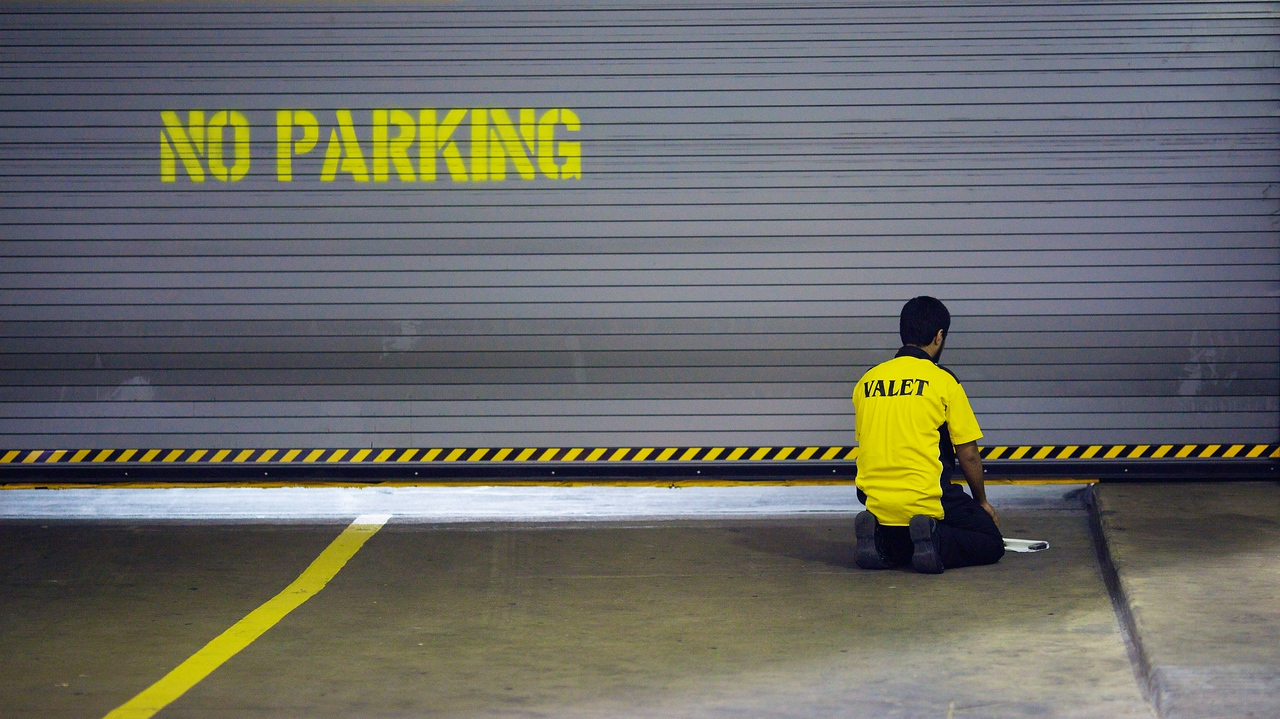 A Muslim parking valet seeks a quiet moment to pray near a dormant parking garage entrance one evening.<br /> (Houston, TX.)