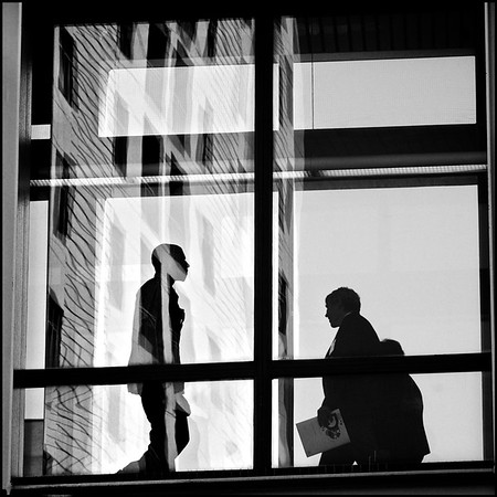 Minnesota - Silhouettes of people walking through reflections as they take an aerial crosswalk.