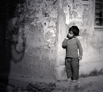 A little girl peeking around a corner in Kathmandu, Nepal.
