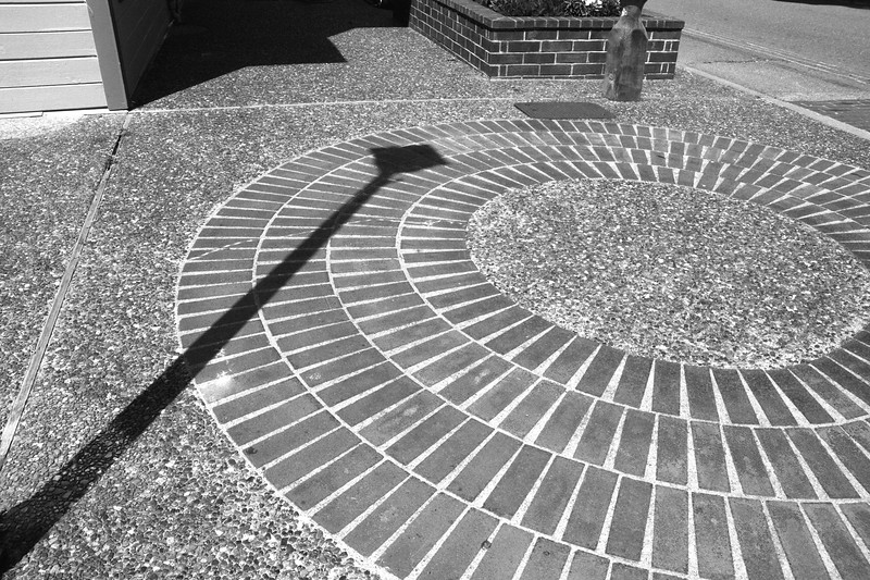 Untitled<br /> I like the play of the shadow from the street lamp onto the brick pattern here on the sidewalk in Eureka California