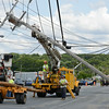 Unitil workers begin repairs to the three telephone poles that were damaged on Summer Street in Fitchburg on Tuesday afternoon after a tractor trailer hit a low hanging wire. SENTINEL & ENTERPRISE / Ashley Green