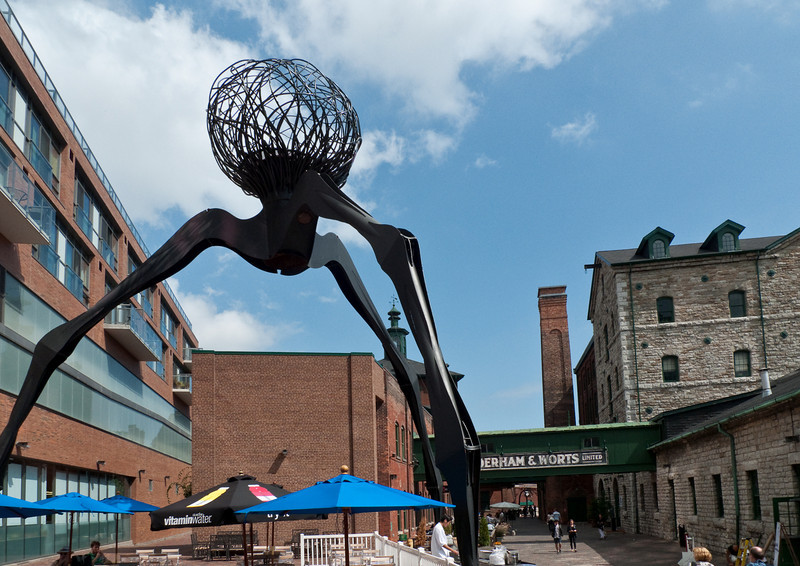 """A """"spider"""" sculpture looms over a cafe patio in Toronto's Distillery District."""