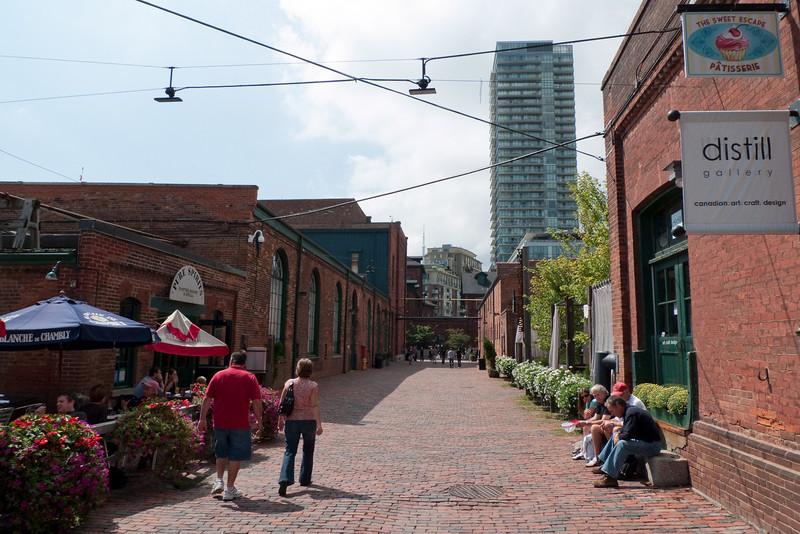 Inside Toronto's Distillery District, a beautiful shopping area built in the various buildings left behind by the Gooderham & Worts Distillery.  A new condo tower, and the top of the CN Tower, can be seen in the distance.
