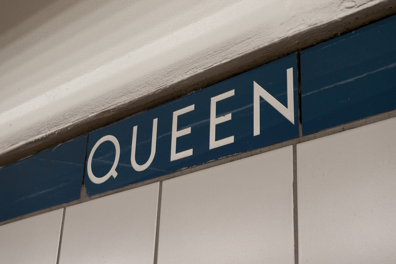 "One of the few surviving examples of the Toronto Subway's original vitrolite tiles can be found in the blue strip near the ceiling of Queen station's platform.  The tiles have an interesting, ""glassy"" reflective quality and are no longer manufactured.  Notice also the unique 50s modernist font designed for the line's 1954 opening."