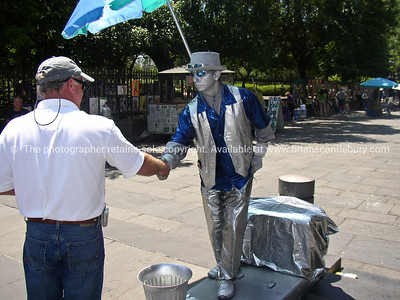Street performer, silver man, on street beside Jackson Square, New Orleans, USA. Shaking hands with tourist.