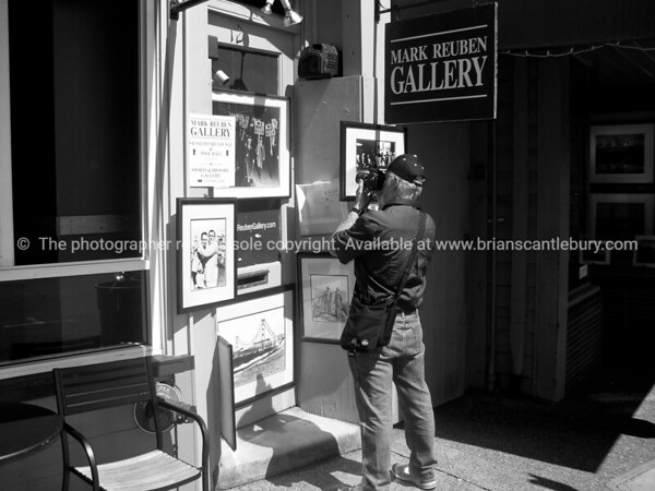 Street scene in black and white. Photographer photographing photographs and other pictures outside a Sausalito gallery.