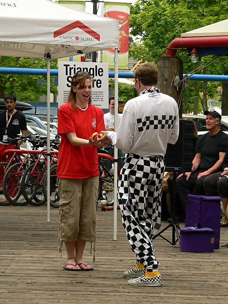 """Series """"The Juggler"""" #1 of 6<br /> <br /> At Granville Island in Triangle Square near the Public Market.  This young lady volunteered.  Here the Juggler is setting her up for her first """"act"""".<br /> <br /> I ran into him again the following day at a different venue.  He is formally known as """"The Checkerboard Guy"""".  Check out his website... <a href=""""http://www.checkerhead.com"""">http://www.checkerhead.com</a><br /> <br /> ."""