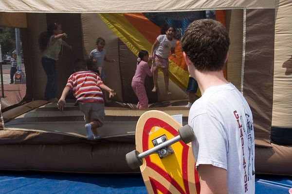 """long board skater wondering if he's too old to try the moon bounce in the middle of Mount Pleasant street - this photo appeared in the <a href=""""http://www.washingtonpost.com/wp-dyn/content/article/2005/07/01/AR2005070101016.html"""">Blog City</a> feature of the Washington Post Sunday magazine on July 3rd 2005."""