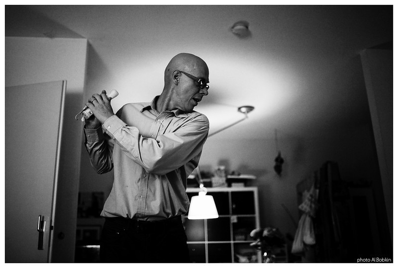 man playing virtual golf at home