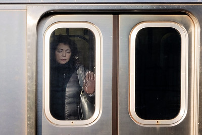 A quick nap while the train is stopped. Early on a Saturday in Brooklyn.