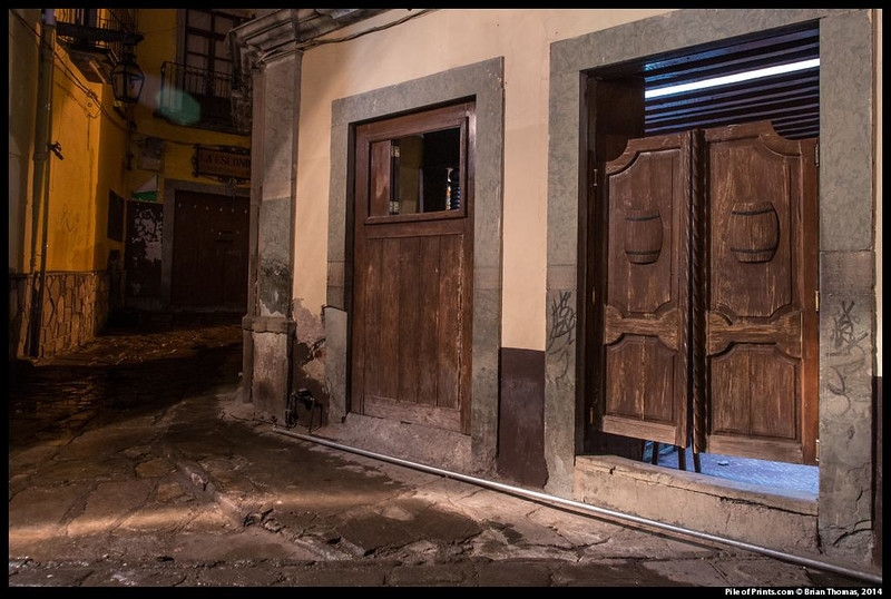 The next photo looks into this working class bar from the open window to the left of the saloon doors .